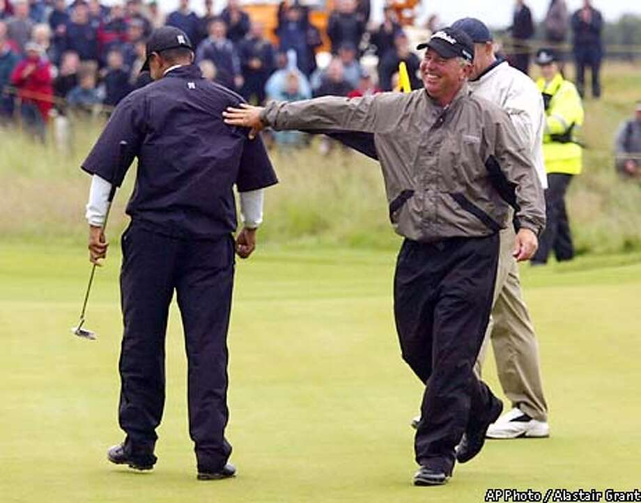 Mark O'Meara of the United States, right, pats his playing partner Tiger Woods on the back after Woods scored his only birdie of the third round of the Golf Championship on the 17th hole at Muirfield golf course in Scotland, Saturday, July 20, 2002. Woods scored a 10-over par 81 to go 6-over par for the tournament. (AP Photo/Alastair Grant) Photo: ALASTAIR GRANT