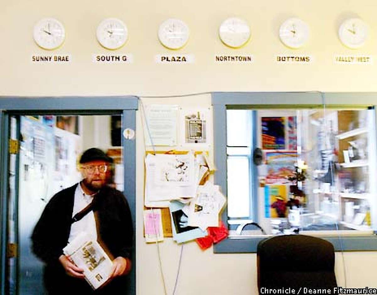 Kevin Hoover, editor and publisher of the Arcata Eye newspaper walks through the small newsroom. On the wall behind him is joke featuring six clocks, each showing a different neighborhood of the small town of Arcata as if in different time zones, but all showing the same time. Hoover is known for writing the police blotter in a very humorous and poetic style. CHRONICLE PHOTO BY DEANNE FITZMAURICE