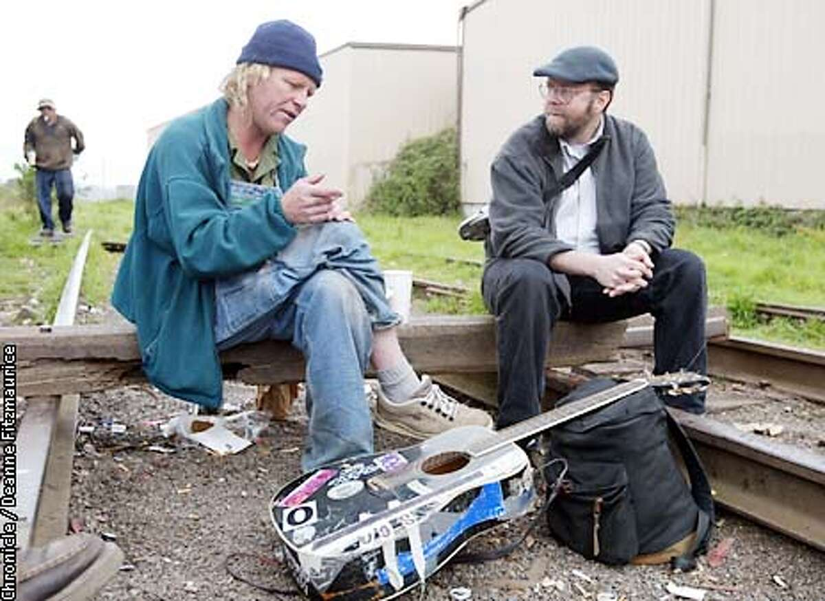 Kevin Hoover, (right) editor and publisher of the Arcata Eye newspaper sits on the railroad tracks on the edge of the town of Arcata and talks with Dan Stephens known as Guitar Dan. Dan and his friends are known as the Fun Bunch in the poetic police blotter that Hoover writes for the weekly newspaper. CHRONICLE PHOTO BY DEANNE FITZMAURICE