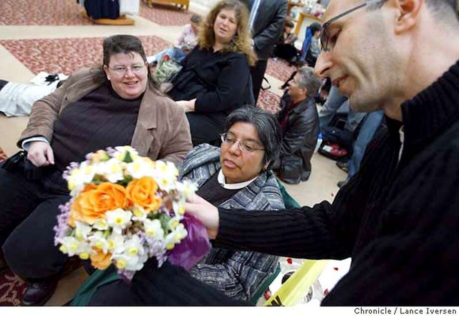 SAMESEX154_LI.JPG event on 2/20/04 in SAN FRANCISCO. Flowers in the Heartland is a new program fuelled by the web in which people from the Midwest call florists in San Francisco to deliver flowers to same sex couples getting married at City Hall. Michael Ritz from Church Street Flowers (right) delivers flowers to Lisa Clayton and Sally Canjura while they waited inside City Hall. The card simply read happy wedding from Minnesota. By Lance Iversen /The San Francisco Chronicle Photo: Lance Iversen