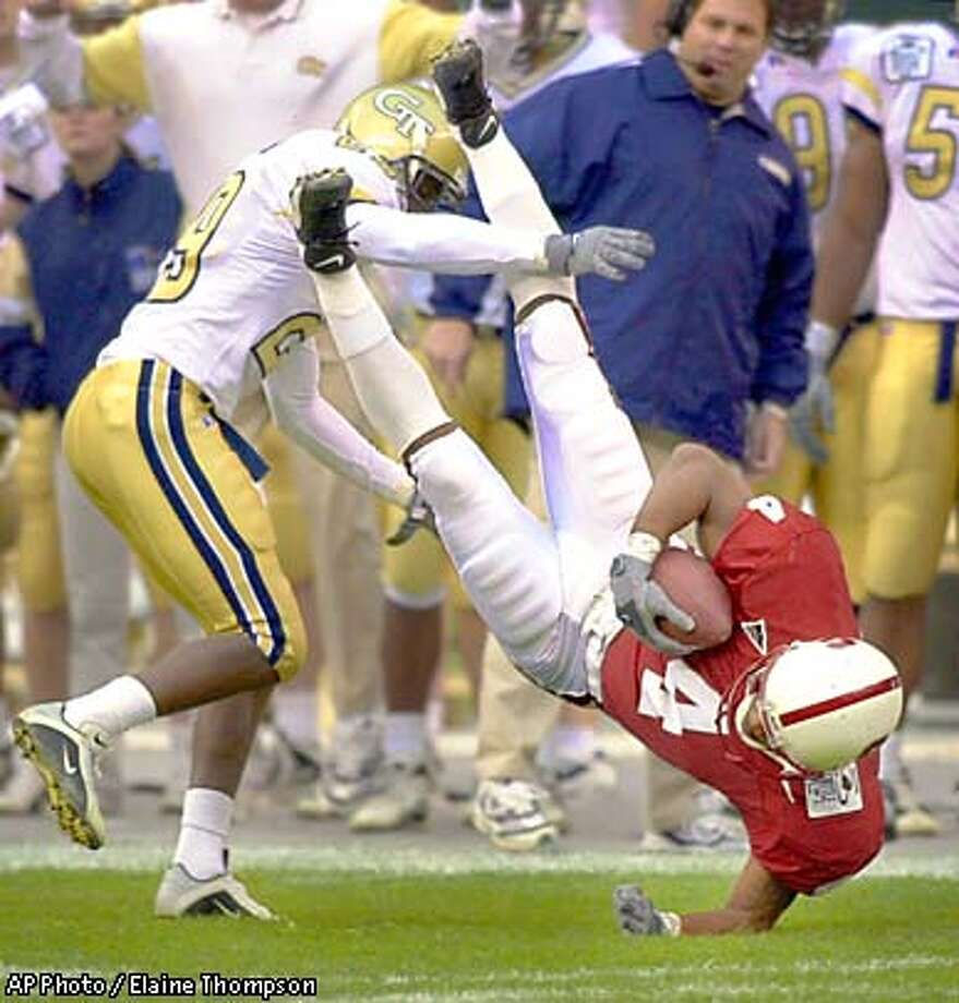 Stanford's Ryan Wells (4) is upended by Georgia Tech's Marvious Hester on a first-down catch during the first quarter of the Thursday, Dec. 27, 2001, in Seattle. ( AP Photo / Elaine Thompson ) Photo: ELAINE THOMPSON