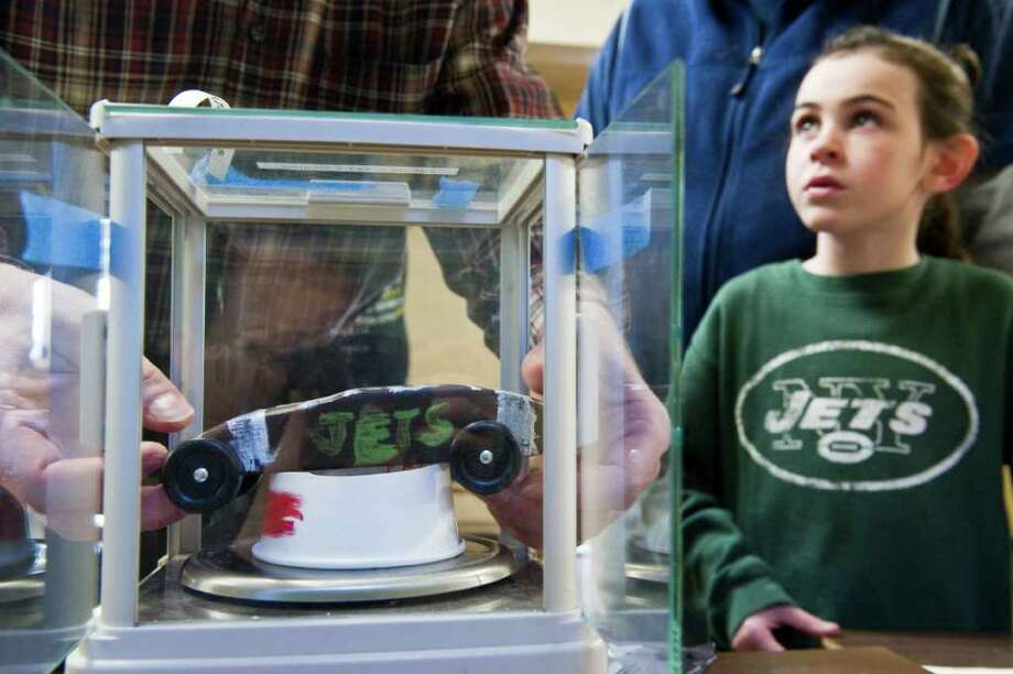 Jets fanatic Mariana McOsker eyes the judge as he determines if the weight of her Jets-themed car is suitable as she checks in for the Girl Scouts' Powderpuff Derby at St. Cecilia's in Stamford, Conn., January 29, 2012. The Girl Scouts' derby, which is modeled after the Boy Scouts' Pinewood Derby, will feature races with small wooden cars they crafted with help from their parents. McOsker will don her Mark Sanchez jersey for the race Saturday. Photo: Keelin Daly / Stamford Advocate