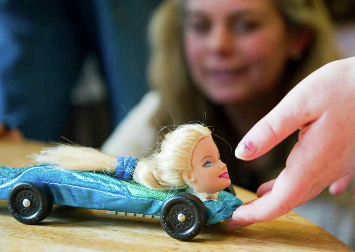 Karen Richman's eyers her daughter Kayla's car as she prepares to check in for the Girl Scouts' Powderpuff Derby at St. Cecilia's in Stamford, Conn., January 29, 2012. The Girl Scouts' derby, which is modeled after the Boy Scouts' Pinewood Derby, will feature races with small wooden cars they crafted with help from their parents. Kayla Richman was washing her Barbie's hair when the doll's head popped off, it was then that her derby car vision was born.