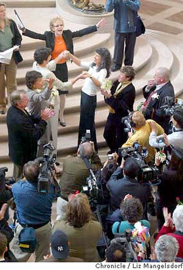 Event at San Francisco on 2/20/04. Corole Migden (arms up) presides over the wedding of Nanci Clarence, left, and Lidia Szajko in the City Hall Rotunda. This was just before her marriage was performed by Mayor Newsom behind closed doors.  Same Sex marriages continue to be performed at City Hall.  Liz Mangelsdorf/ The Chronicle Photo: LIZ MANGELSDORF