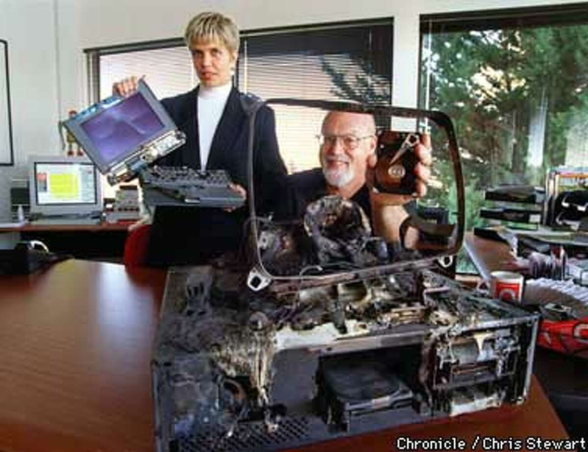 Scott Gaidano, president of DriveSavers, and Nikki Stange who functions as the company data crisis counselor, display ruined computers from which the Novato company successfully retrieved all data stored on the hard drives. The machine framing Gaidano was burned in a fire and the crushed laptop held by Stange was run over by a bus. SAN FRANCISCO CHRONICLE PHOTO BY CHRIS STEWART