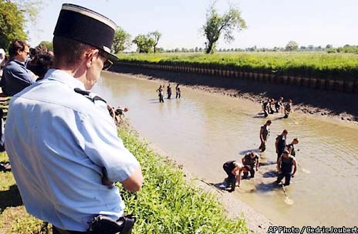 A gendarme, left, looks at French soldiers searching for art objects in a canal in Gerstheim, eastern France , Thursday May 16, 2002. Investigators partly emptied the canal between the Rhone and the Rhine rivers to find objects and paintings stolenfrom different museums around Europe. Stephane Breitwieser, 31, suspected of stealing more than 172 art objects and paintings, has been caught by police but many of the treasures may have been destroyed by the suspects's mother. (AP Photo/Cedric Joubert)