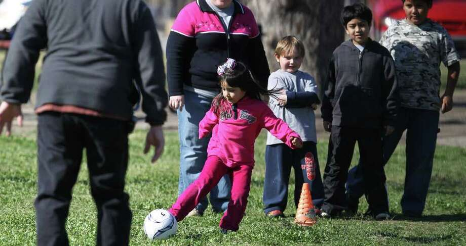 Liz Lopez,5, (ribbon in hair) takes part in a game of kickball Sunday January 29, 2012 at Brakenridge Park with friends and family from Durango Seventh-Day Adventist Church. Church pastor Robin Lopez says the youth group tries out a different park each Sunday. Behind Liz Lopez are (left to right) David Lopez,5, Mel Rey,9, and Gabriel Hernandez,9. John Davenport/San Antonio Express-News Photo: John Davenport, SAN ANTONIO EXPRESS-NEWS