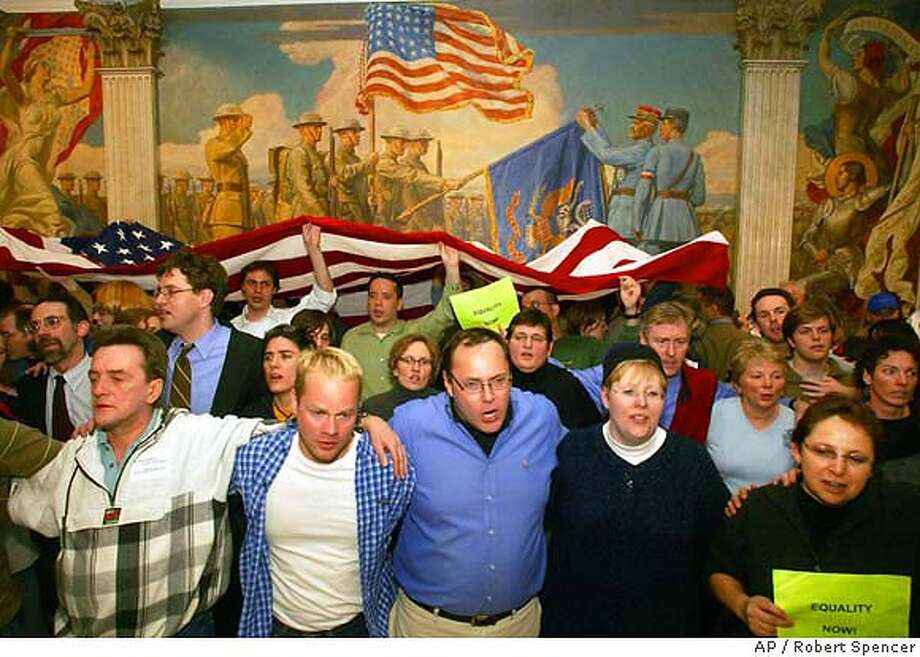 """Supporters of gay marriage link arms and sing """"God Bless America"""" at the Statehouse in Boston late Thursday, Feb. 12, 2004. A weary Massachusetts Legislature suspended debate Thursday on a proposed gay marriage ban after two days of tense negotiations. The constitutional convention will resume March 11. (AP Photo/Robert Spencer) Photo: ROBERT SPENCER"""