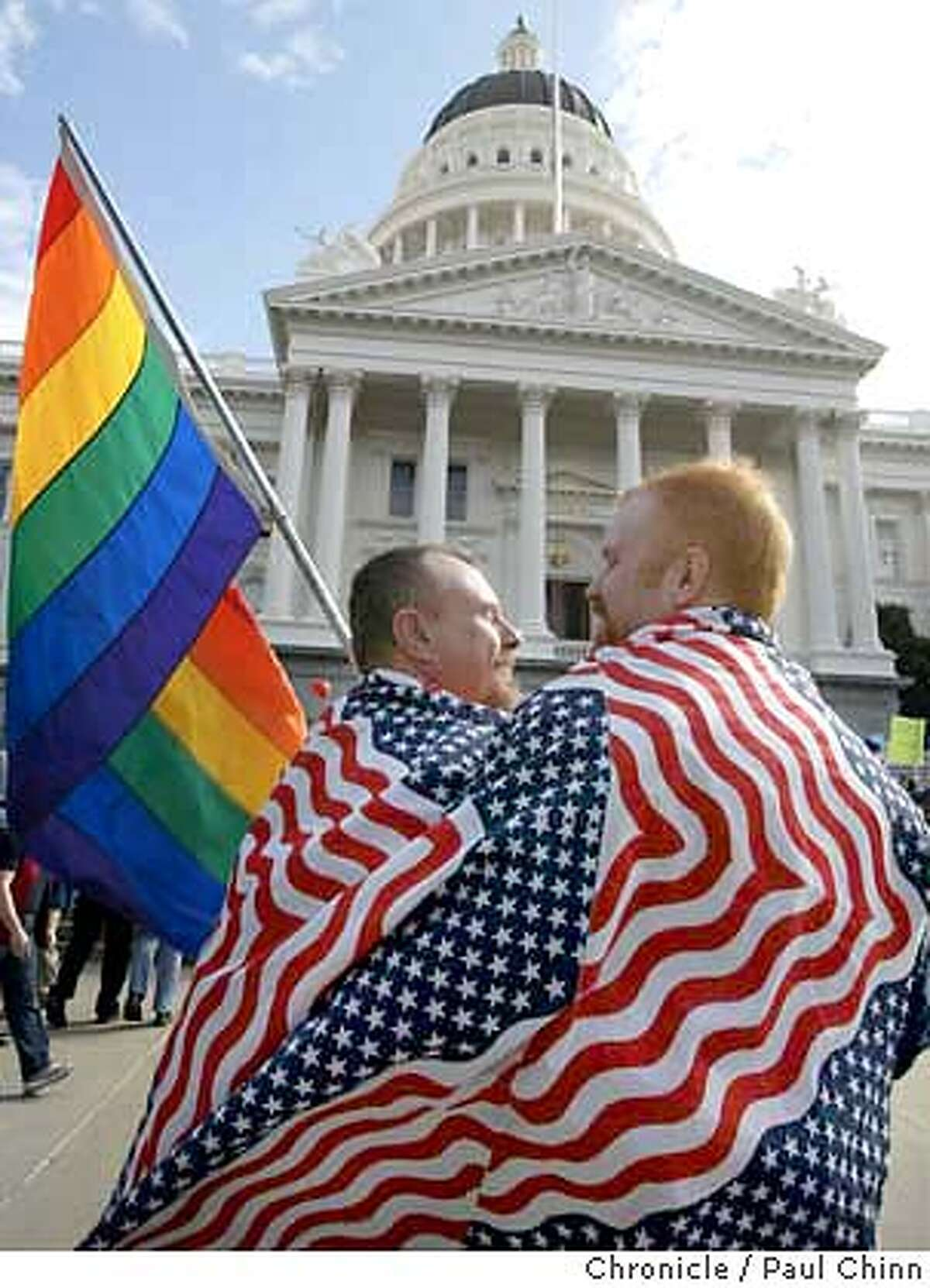Mike Holland (left) and his partner Jim Gatteau draped themselves in red, white, blue - and rainbow - for the rally. The couple, together for eight months, don't want to rush into a marriage. Supporters of same-sex marriages held a rally in front of the State Capitol on 2/14/04 in Sacramento. PAUL CHINN / The Chronicle