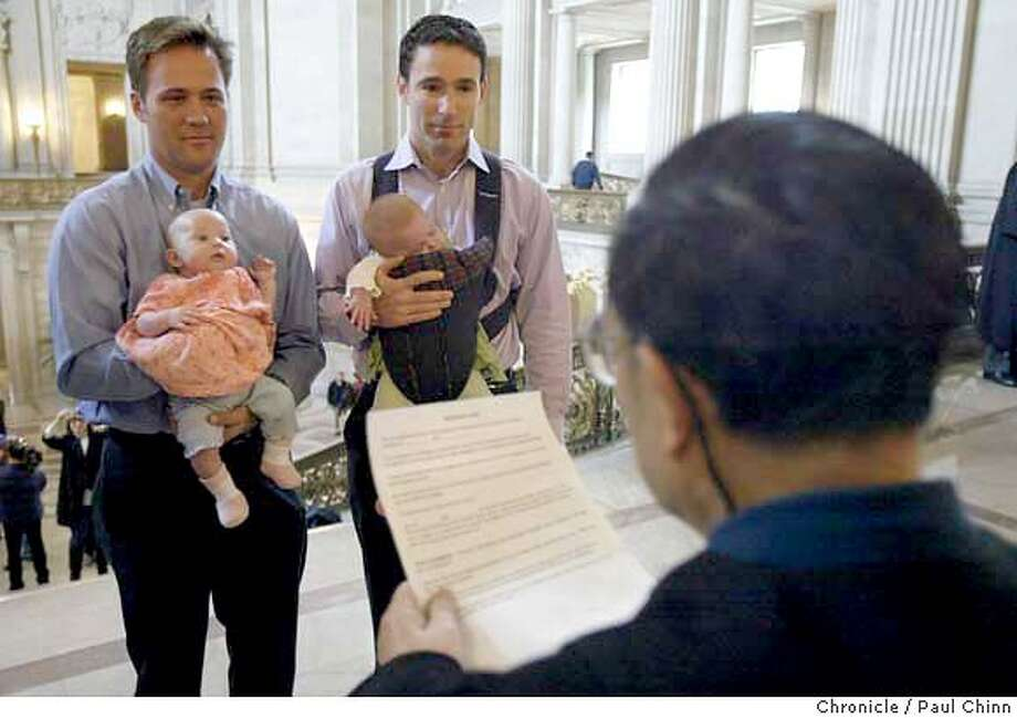 gaymarriage_136_pc.JPG Holding the twin daughters Sophia and Elizabeth, Eric Etherington (left) exchanges marriage vows with Doug Okun in front of marriage commissioner Richard Ow on Friday. Same sex couples waited up to two hours to get legally married at City Hall on 2/13/04 in San Francisco. PAUL CHINN / The Chronicle Photo: PAUL CHINN