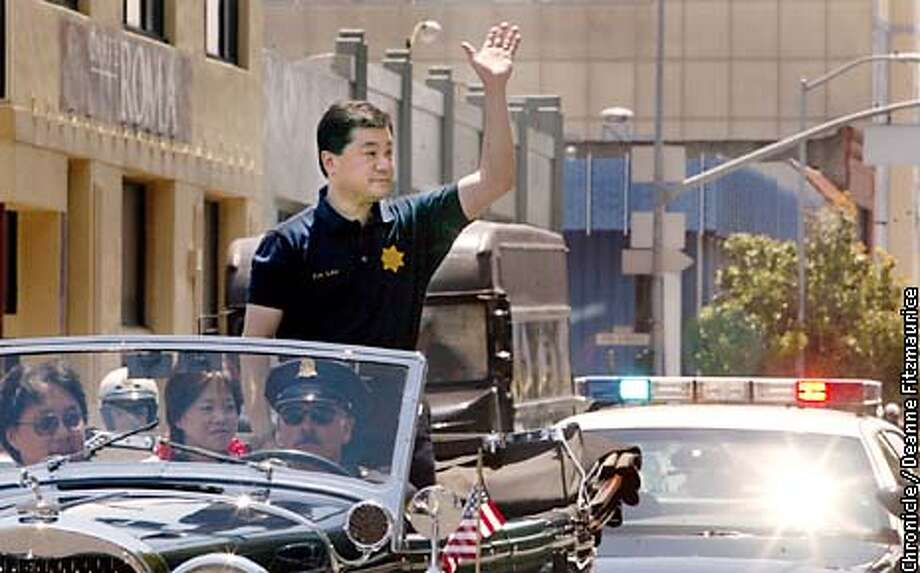 On Police Chief Fred Lau's last day as chief he rides through the city in a classic convertible. He is passing by the Hall of Justice and waving to a group of officers and spectators and lion dancers.  CHRONICLE PHOTO BY DEANNE FITZMAURICE Photo: DEANNE FITZMAURICE