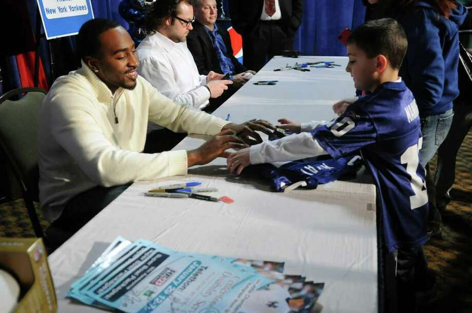 New York Giants Hakeem Nicks, left, signs a jersey for Ggegory Kayayan, 8, of Slingerlands  at the 52nd Annual Center for Disability Services Telethon on Sunday, Jan. 29, 2012 at the Holiday Inn in Albany, NY.  New York Yankees Joba Chamberlain, second from left, was also at the event signing autographys (Paul Buckowski / Times Union) Photo: Paul Buckowski