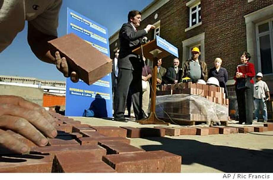 California Insurance Commissioner John Garamendi, center, speaks during a news conference as a brick mason paves the ground for the Science Center Elementary School, Tuesday, Feb. 10, 2004, in Los Angeles. Garamendi unveiled a comprehensive legislative package aimed at reforming the state's workers compensation system. (AP Photo/Ric Francis) Photo: RIC FRANCIS