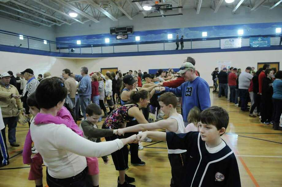 Melissa Watts, left, of Clifton Park holds her daughter Ashlyn Watts, 4, as she fits bumps with Danny Deasy, 8, of Round Lake as the two along with over 400 other people fist bump for an unofficial record at the Southern Saratoga YMCA on Sunday, Jan. 29, 2012 in Clifton Park, NY.  The final count of people performing the fist bumps simultaneously was 428.  The event was organized by the Times Union.  The event will have to be certified by  Guinness before it becomes official.  (Paul Buckowski / Times Union) Photo: Paul Buckowski