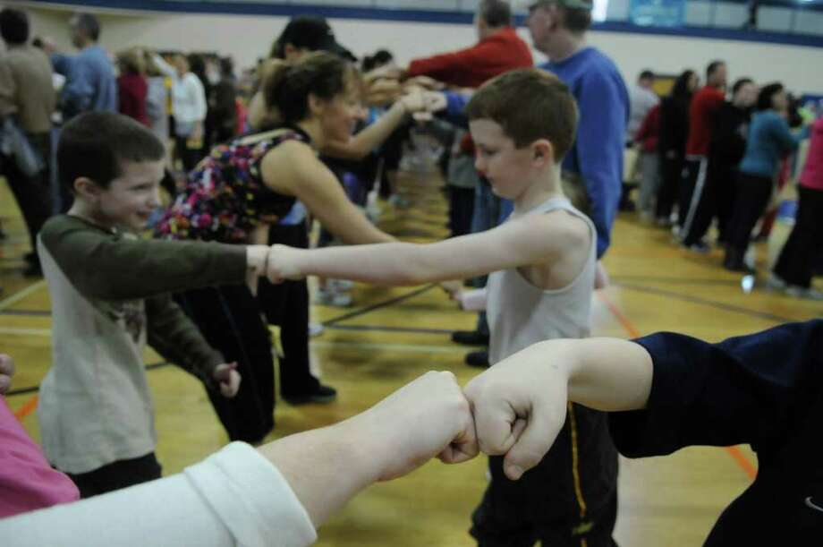 Over 400 people fist bump for an unofficial record at the Southern Saratoga YMCA on Sunday, Jan. 29, 2012 in Clifton Park, NY.  The final count of people performing the fist bumps simultaneously was 428.  The event was organized by the Times Union.  The event will have to be certified by  Guinness before it becomes official.  (Paul Buckowski / Times Union) Photo: Paul Buckowski