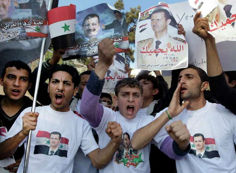 Protesters shout slogans as they carry pictures of Syrian President Bashar Assad and Syrian flags during a demonstration in front of the Russian Embassy in Beirut, Lebanon, Sunday, Jan. 29, 2012, to express gratitude for the Russian position in support of Syria.  Russia has said it will use its Security Council veto to block any resolution threatening Syria with sanctions or lacking a clear ban on any foreign military interference. Photo: Bilal Hussein, AP / AP