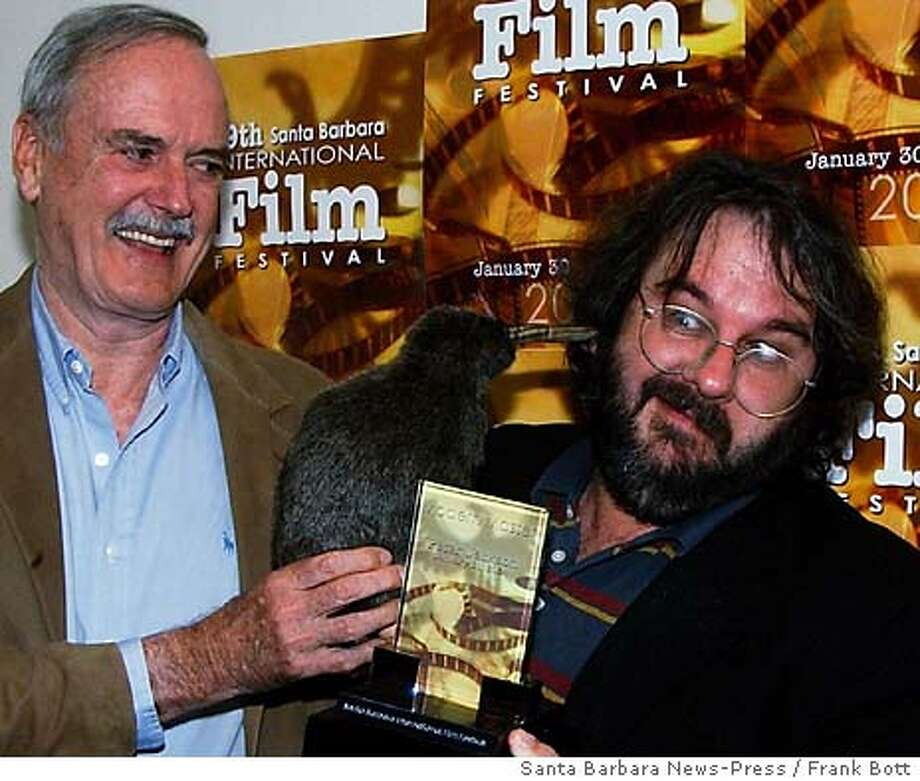 "Actor-comedian John Cleese, left, presents a stuffed kiwi and the Modern Masters award from the Santa Barbara International Film Festival to Peter Jackson, director of ""The Lord of the Rings,"" Saturday night, Jan. 31, 2004, at the Arlington Theater in Santa Barbara, Calif., during a Tribute to Jackson. (AP Photo/Santa Barbara News-Press / Frank Bott) STAND ALONE PHOTO Photo: FRANK BOTT"