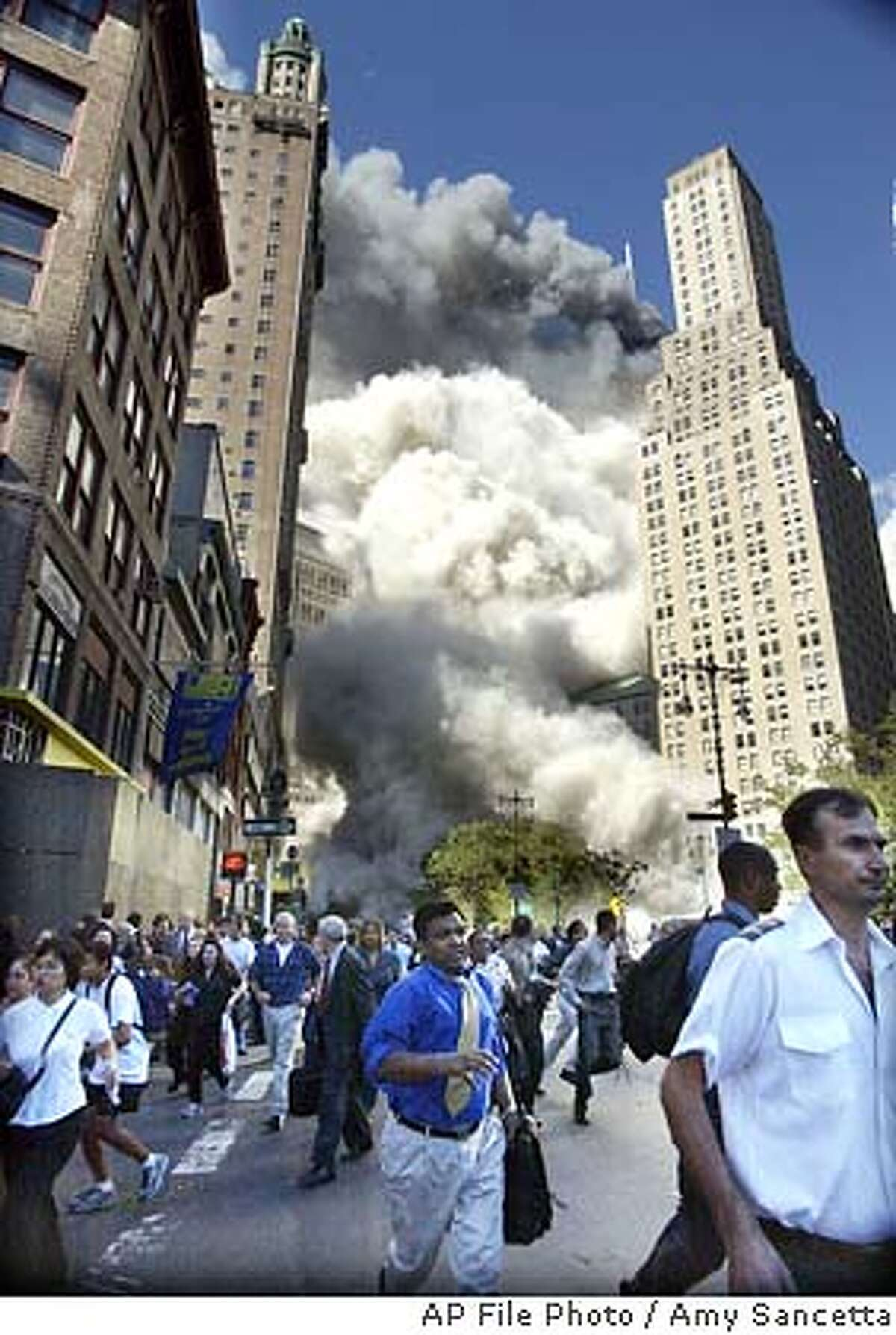 Pedestrians flee the area of the World Trade Center as the center's south tower crashes following a terrorist attack on the New York landmark Tuesday, Sept. 12, 2001. (AP Photo/Amy Sancetta)