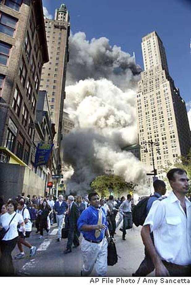Pedestrians flee the area of the World Trade Center as the center's south tower crashes following a terrorist attack on the New York landmark Tuesday, Sept. 12, 2001. (AP Photo/Amy Sancetta) Photo: AMY SANCETTA
