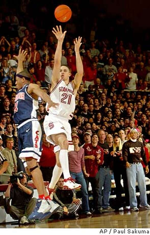 Stanford forward Nick Robinson makes the winning three-point shot in front of Arizona forward Andre Iguodala, left, in the final second of Stanford's 80-77 win over Arizona, Saturday, Feb. 7, 2004 in Stanford, Calif. At far right is golfer Tiger Woods. (AP Photo/Paul Sakuma) Photo: PAUL SAKUMA