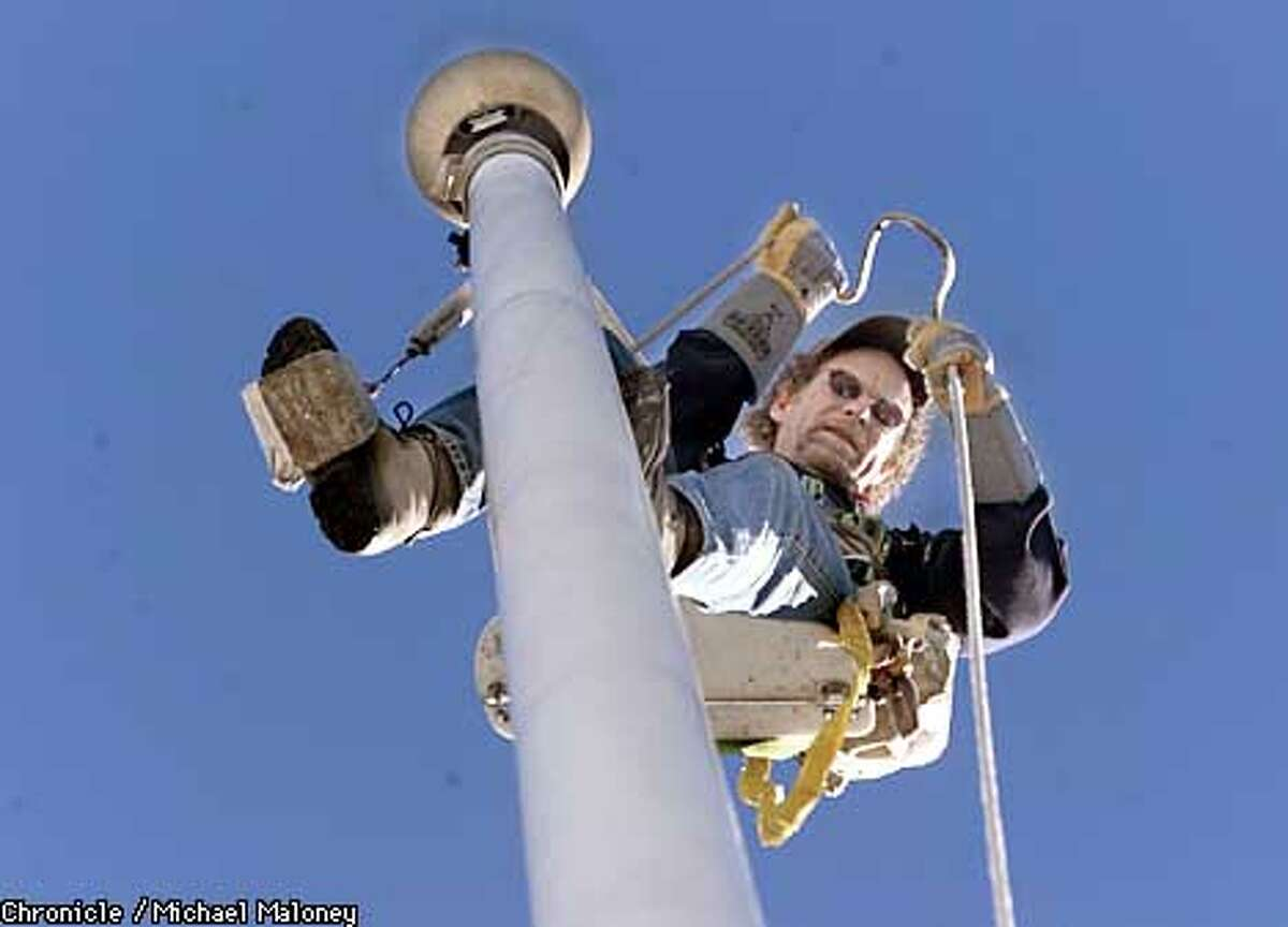 Jim Phelan replaces the flag rigging on top of a 70 foot fiberglass flagpole on top of the Mark Hopkins Hotel in SF. On a windy day, the tip of the flagpole can sway 5 feet in each direction. Phelan is a steeplejack who climbs up anything for a living. His business, the J.C. Phelan Company dates back to his grandfather, who worked as a steeplejack in Waterford, Ireland, over 100 years ago. CHRONICLE PHOTO BY MICHAEL MALONEY