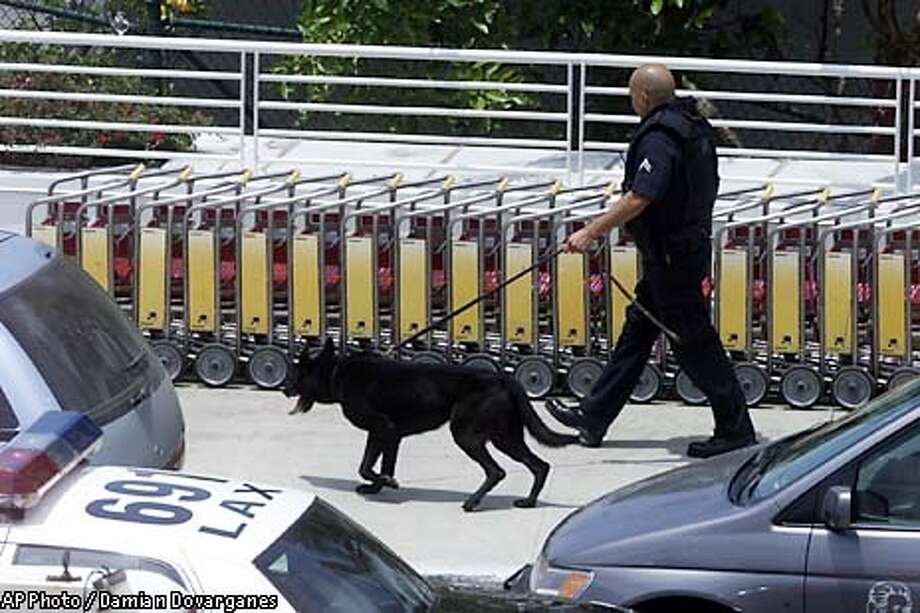 An Los Angeles Police officer and his K-9 partner roam the walkways outside the Los Angeles International Aiport, Thursday, July 4, 2002, after a gunman opened fire at an El Al Airlines ticket counter earlier in the day. Three people were killed, including the attacker, who was shot dead by an airline security guard, authorities said. Three people were wounded, and thousands were evacuated from the international terminal. One person was arrested, police said. (AP Photo/Damian Dovarganes) Photo: DAMIAN DOVARGANES