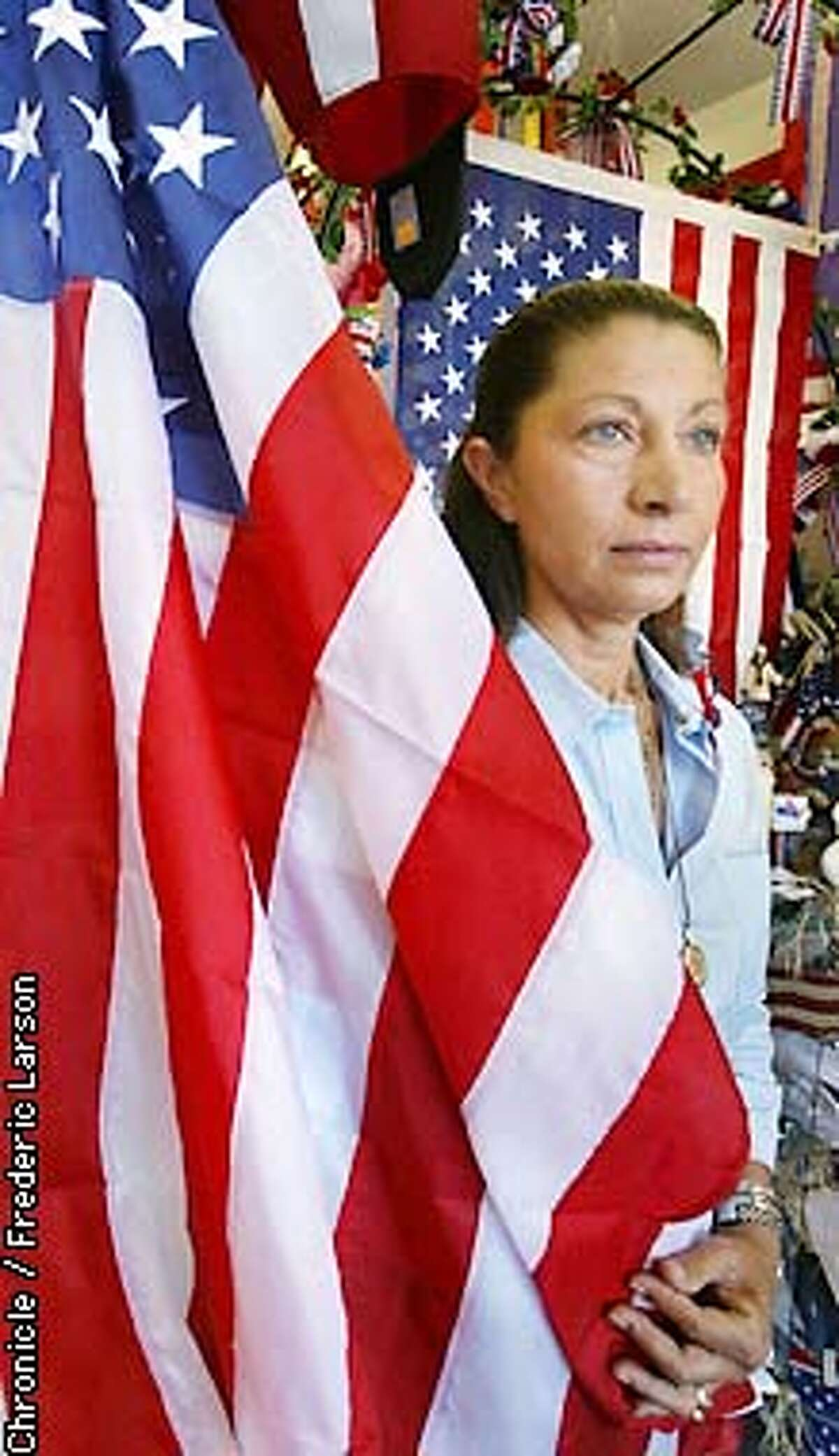: Judy's Flag City has been selling them for 10 years in her small shop, overflowing with U.S. flags, bunting, and a huge assortment of other paraphernalia. On Sept. 11, Judy Sheldon, a Greek immigrant, sold 3,000 flags. Last July 4, she sold about 500 flags. This year, after 9/11, she'll sell 1,000. Patriotism is on the rise. Chronicle photo by Frederic Larson