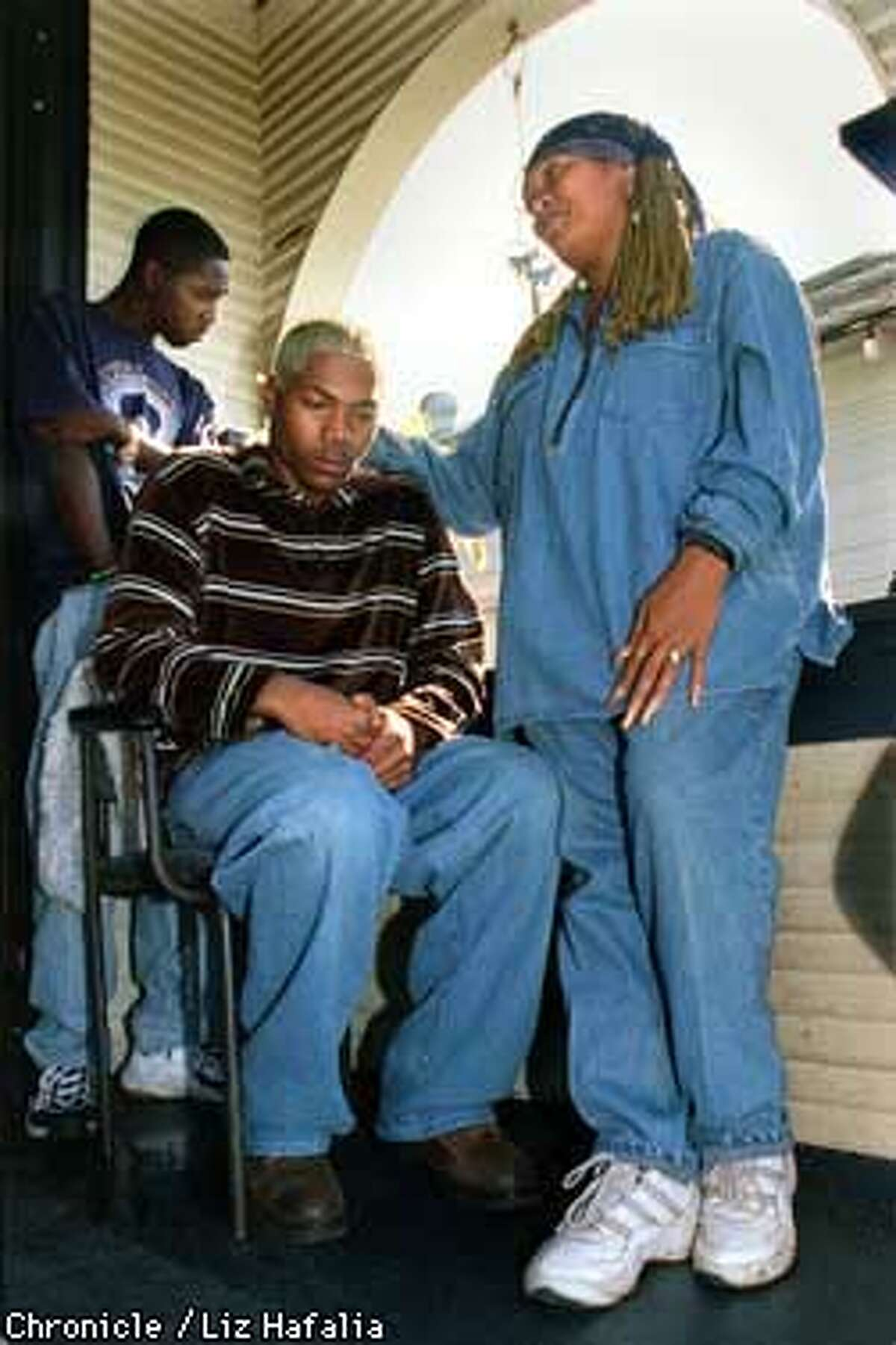(seated)Shelton Lee, 18 years old, brother of Loeshe Lacy, is comforted by Fely Ward (right), godmother of Loeshe, on his front porch at home. A cousin, Willie Stanley (back left) is behind him. Liz Hafalia