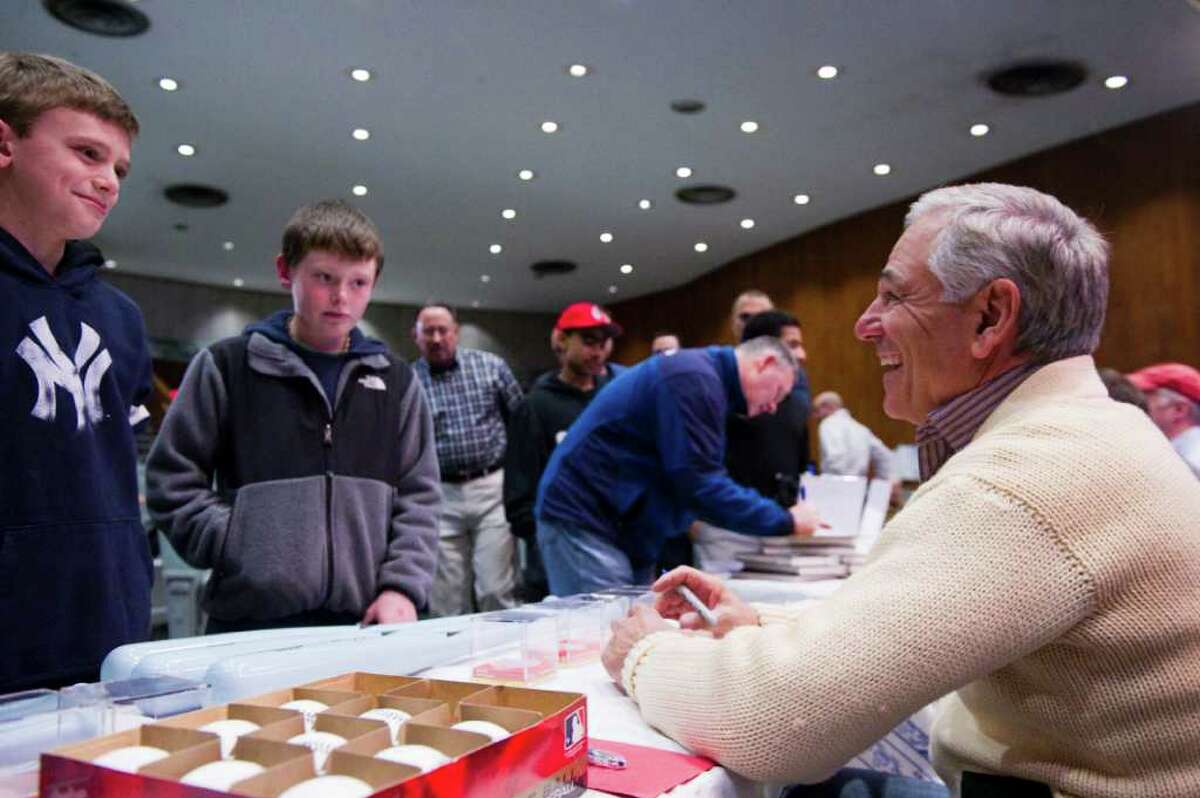 """Boston Red Sox Manager Bobby Valentine hassles Yankee fan John Hogan, left, as Mike McLaughlin looks on as Valentine signs memorabilia at his alma mater Rippowam High School in Stamford, Conn., January 29, 2012. Valentine talked baseball with broadcaster Ed Randall in a fundraising event for Randall's charity """"Fans for the Cure"""" aimed at fighting prostate cancer with early detection."""