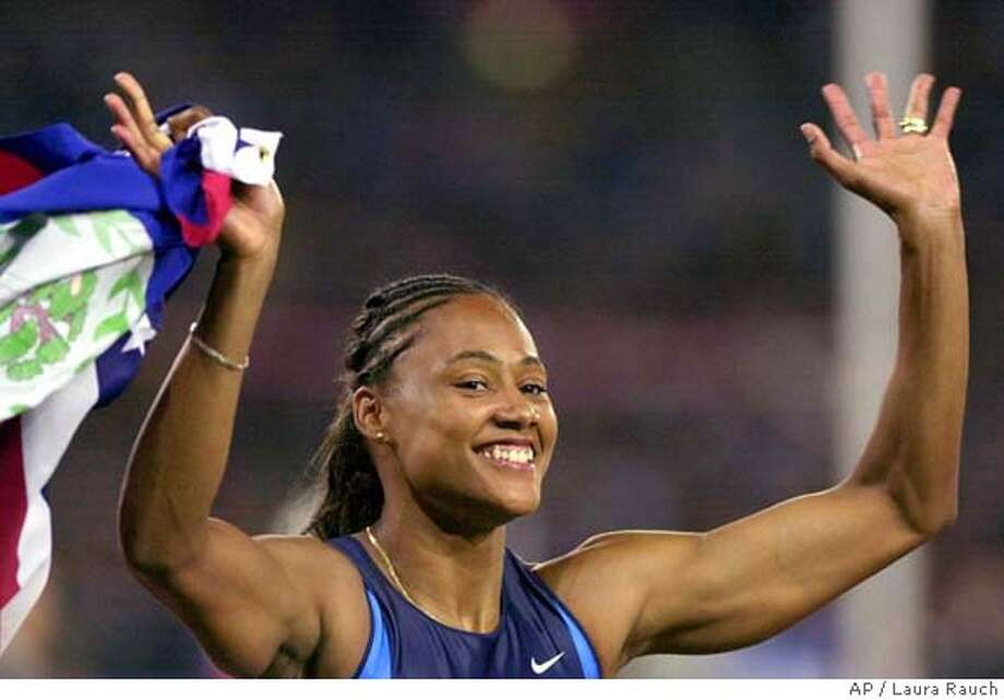 Marion Jones of the United States celebrates after she won the women's 100 meters at Olympic Park during the 2000 Summer Olympics in Sydney, Saturday, Sept. 23, 2000. (AP Photo/Laura Rauch) DIGITAL IMAGE Photo: LAURA RAUCH