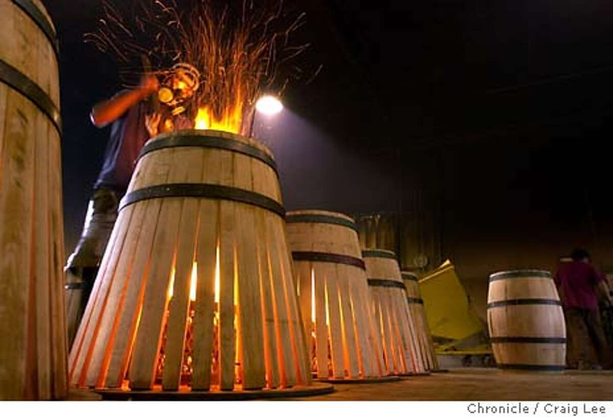 Oak wine barrels being fire roasted at Demptos Napa Cooperage at 1050 Soscol Ferry Road in Napa. Photo of Victor Lopez putting more wood to burn inside the barrel to roast it. Event on 2/3/04 in Napa. CRAIG LEE / The Chronicle