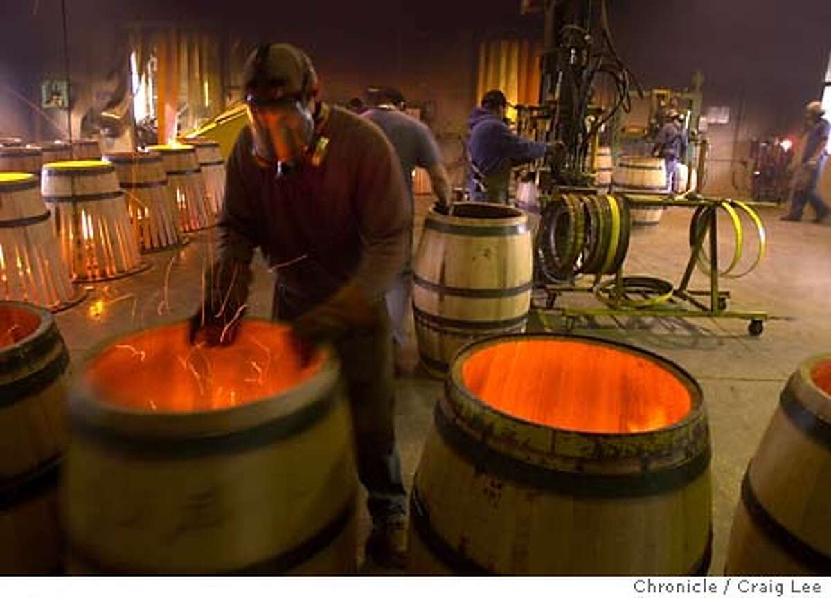 Oak wine barrels being fire roasted at Demptos Napa Cooperage at 1050 Soscol Ferry Road in Napa. Photo of Desiderio Torres in the foreground roasting barrels. Event on 2/3/04 in Napa. CRAIG LEE / The Chronicle