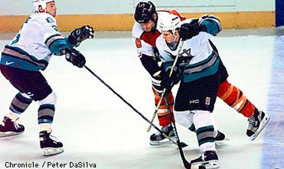 Philadelphia Flyers Eric Lindros gets checked by Sharks Shean Donovan as he and fellow teammate Doug Bodger go after the puck in the first period of their game with the Flyers. Chronicle Photo By: Peter DaSilva Photo: Peter DaSilva