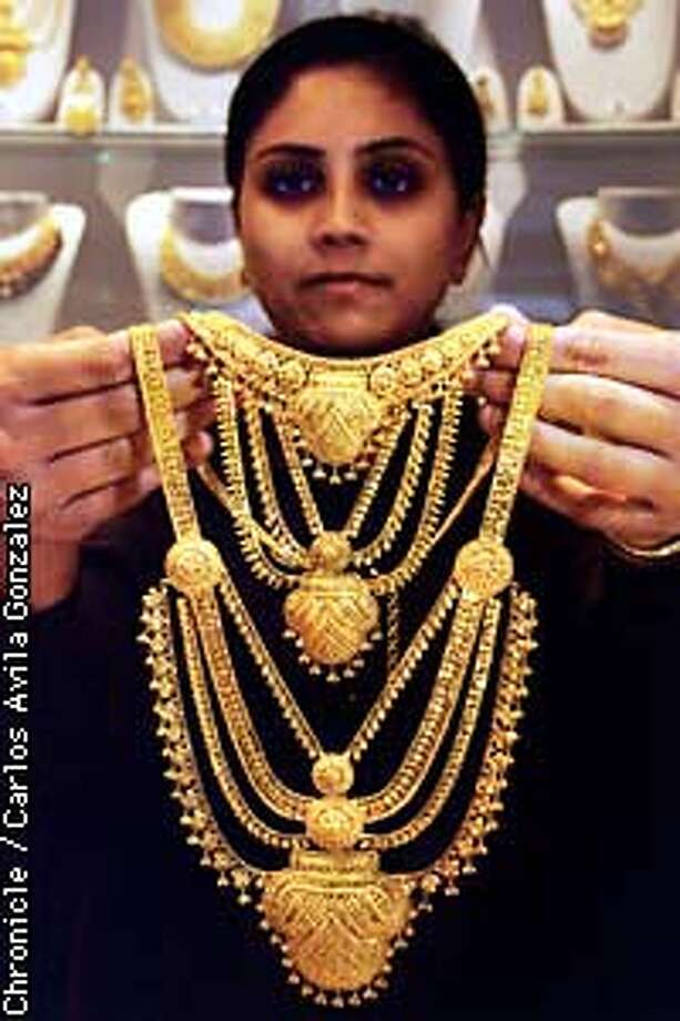 Anupa Thakkar of the Gold Palace holds up a Rami Har, or Queen's Necklace, a 22-karat gold piece sold in the store on University. University Avenue is sprinkled with shops specializing in Indian clothes, food, jewelry, and other items, making it very popular with the Indian community as far as Los Angeles. (CHRONICLE PHOTO BY CARLOS AVILA GONZALEZ) Photo: CARLOS AVILA GONZALEZ