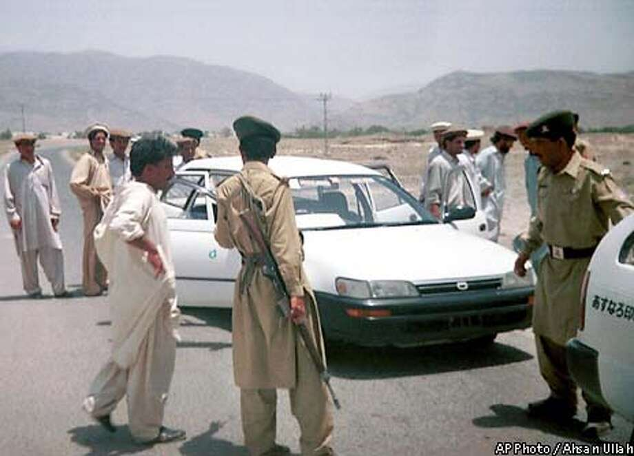 """Pakistani paramilitary troops check vehicles in Pakistan's tribal area, South Waziristan, searching for al-Qaida fugitives fleeing from neighboring Afghanistan, Monday, July 1, 2002. A top Pakistani Islamic cleric warned Monday of """"riots and civil disobedience"""" if President Gen. Pervez Musharraf does not halt the search for al-Qaida fugitives in the fiercely independent tribal regions. (AP Photo/Ahsan Ullah) Photo: AHSAN ULLAH"""