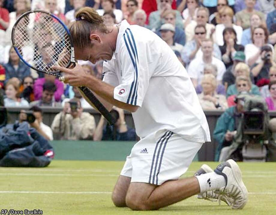 Belgium's Xavier Malisse falls to his knees after defeating Britain's Greg Rusedski, 3-6, 6-3, 3-6, 6-3, 6-4, in their Men's Singles, fourth round match on the Centre Court at Wimbledon, Tuesday July 2, 2002.(AP Photo/Dave Caulkin) Photo: DAVE CAULKIN