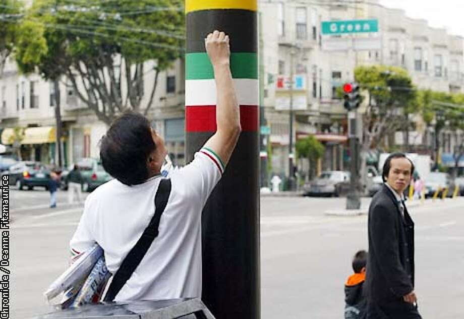 Passersby watch as Ed Lee puts a tiny American flag over an Italian flag on a lampost in North Beach. CHRONICLE PHOTO BY DEANNE FITZMAURICE Photo: DEANNE FITZMAURICE