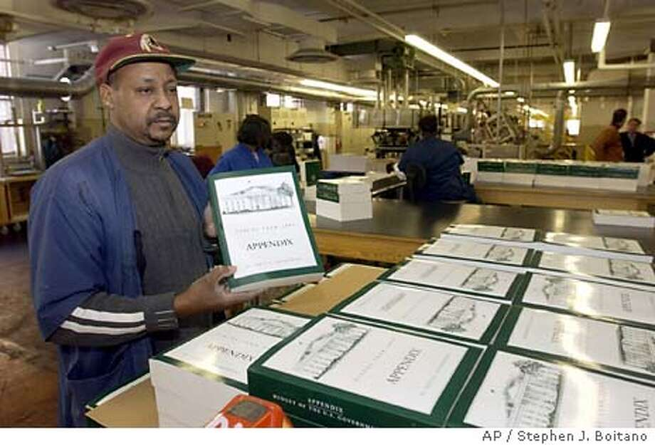 """Government Printing Office employee Michel Bruce displays a copy of President Bush's fiscal 2005 federal budget books at the GPO in Washington Wednesday, Jan. 28, 2004. The president is rolling out his budget for 2005 fresh off a season of wins on what he wanted for this year and confidant he's the exception to the adage """"dead on arrival"""" often applied his predecessors' spending proposals. (AP Photo/Stephen J. Boitano) Photo: STEPHEN J. BOITANO"""