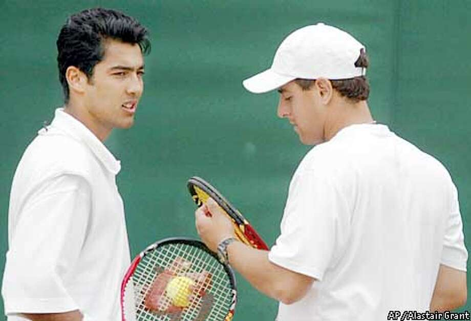 Aisam Ul-Haq Qureshi, left, a Muslim from Pakistan, speaks with his partner, Amir Hadad, a Jew from Israel, during the Men's Doubles match against the Czech pair Martin Damm and Cyril Suk, at Wimbledon Monday July 1, 2002. Qureshi has faced criticism at home, with the Pakistan Sports Board threatening to suspend him for playing with an Israeli. Hadad said he had heard only positive reaction from Israel. (AP Photo/Alastair Grant) Photo: ALASTAIR GRANT