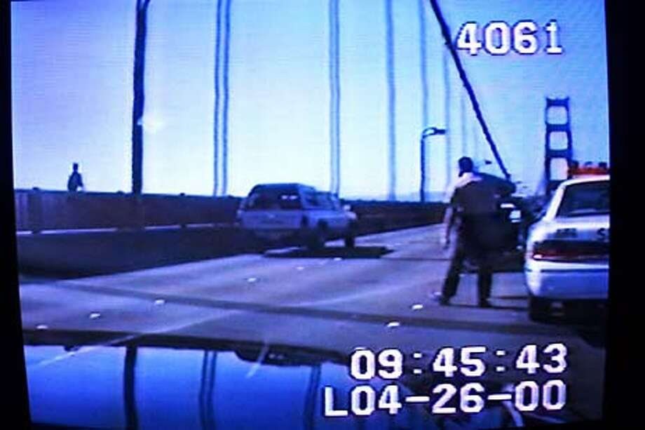 CHASE02-26APR00-MN-CS Brian Alexander Ward, 39, a high risk sex offender, prepares to leap to his death off the Golden Gate Bridge (at far) this morning as Marin Sheriff's Deputy Walter Mazar attempts to stop him. The image was from an in-dash video camera in a Mill Valley Police car. Ward crossed over into oncoming traffic on the bridge before jumping from it as it faced the wrong way. Sausalito Police attempted to arrest Ward in a stakeout, but he eluded them before being pursued onto the bridgeby Sausalito, Mill Valley and Marin County police agencies. SAN FRANCISCO CHRONICLE PHOTO BY CHRIS STEWART Photo: CHRIS STEWART