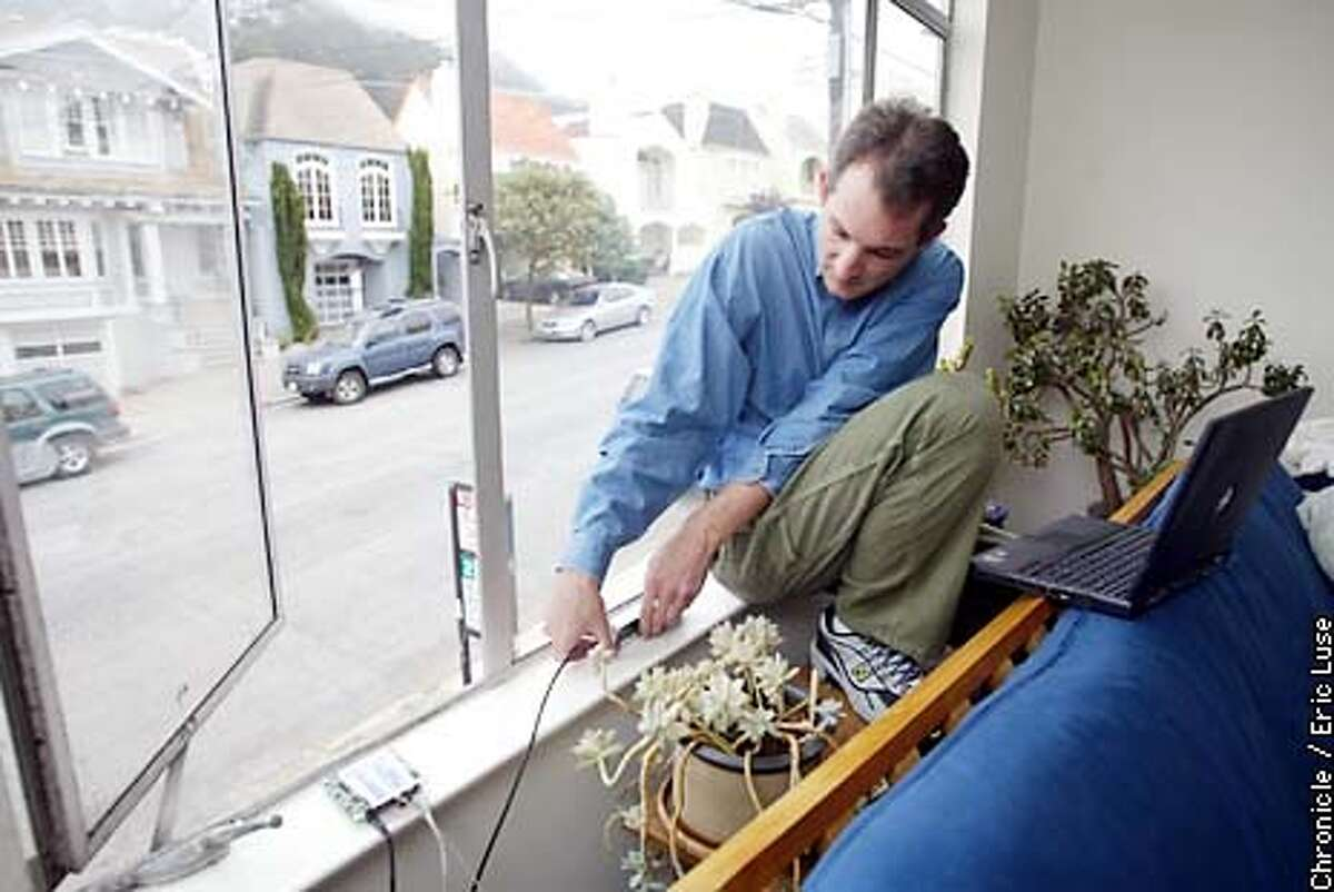 Dan Augustine, co-founder of SF WIreless adjust the antenna of his system that allows users in his neighborhood to access the internet for free. BY ERIC LUSE/THE CHRONICLE