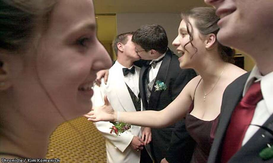 Meet and greet: David Dalpino and Jed Levine steal a kiss outside the prom as their classmates greet one another. They were the school's only gay couple to attend the event together earlier this month. Chronicle photo by Kim Komenich