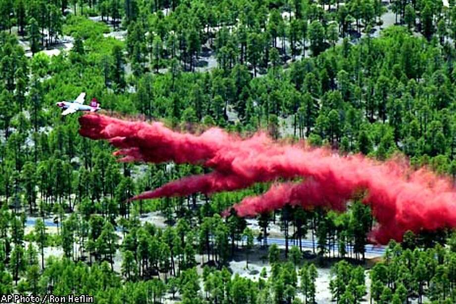 A cargo plane drops a load of flame retardant in Forest Lakes, Ariz., along highway 260 as the wild fire aproaches the small town Wednesday, June 26, 2002. Fire crews reported their first progress Wednesday against the worst wildfire in Arizona history, announcing they had containment lines around 5 percent of the blaze that has burned 373,000 acres and destroyed at least 390 homes. (AP Photo/Ron Heflin) Photo: RON HEFLIN