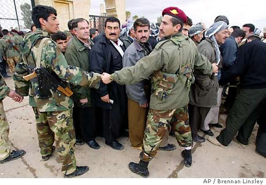 Iraqi Kurdish Peshmerga fighters keep back a crowd of people, as they are screened for weapons and explosives Monday, Feb. 2, 2004 before entering a wake mourning those killed a day earlier in two suicide bombing attacks at holiday political gatherings, killing at least 67 people, in the northern Iraqi Kurdish city of Irbil. Officials said there were 267 people injured in the attacks.(AP Photo/Brennan Linsley) Photo: BRENNAN LINSLEY