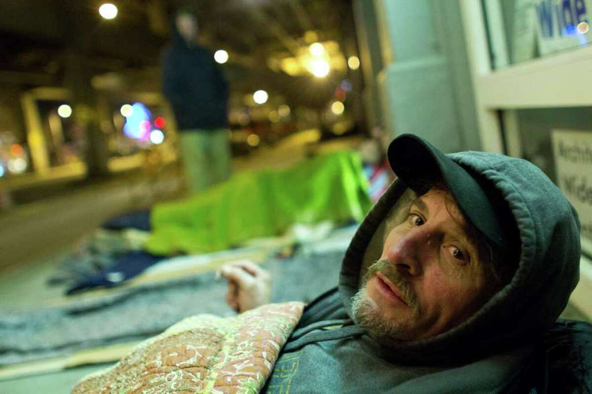 Perry Debell winds down for the evening in his bed made of cardboard and blankets near the Alaskan Way Viaduct in Seattle on Saturday, Jan. 28, 2012. Debell has been in this location for about 10 months and knows the construction workers and shop keepers in the area. Every morning he packs up his belongings by 6:30 a.m., so he does not disturb the business owners and sets off in search of day labor or handouts. He prefers sleeping on the sidewalk instead of in a shelter because he is fearful of bed bugs and the people in the shelters.