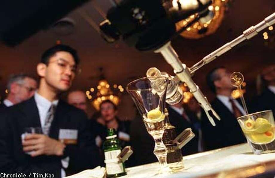 =SRI International's remote surgical instrument pours martini for the crowd at IIC. PHOTO BY TIM KAO/THE CHRONICLE Photo: TIM KAO