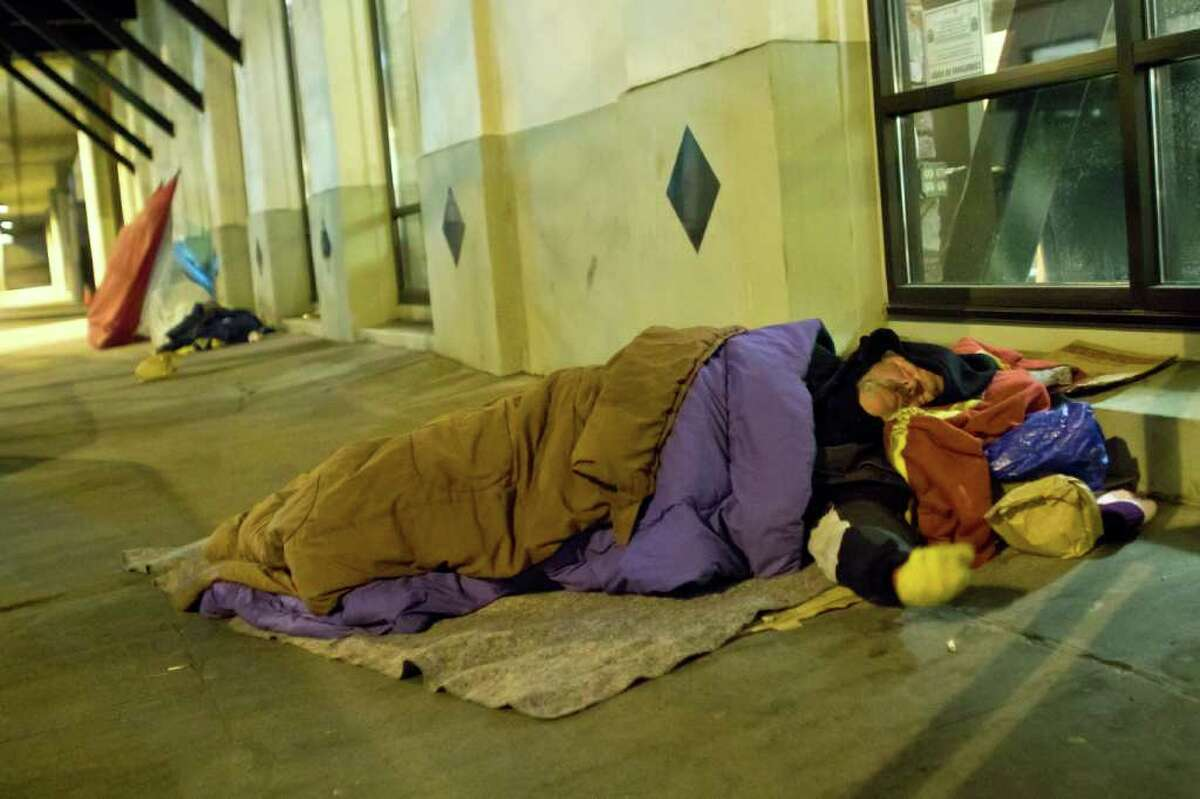 A man sleeps near the Alaskan Way Viaduct in Seattle on Saturday Jan. 28, 2012.