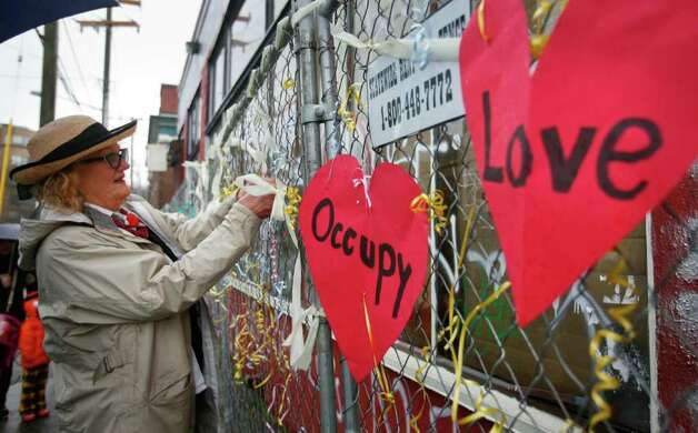 Ann Hirsci ties more ribbons to a fence outside the 10th Ave. and Union St. warehouse before Babylonia Aivaz's wedding to the building on Sunday, Jan. 29, 2012. About 30 people attended Aivaz's wedding, which she says is a gay marriage because the building is a woman.  Aivaz, who was among the Occupy Seattle protesters who wanted to reclaim it as community space, is using the wedding to protest the demolition of the 107-year-old building. An apartment building will be built in its place. Photo: LINDSEY WASSON / SEATTLEPI.COM