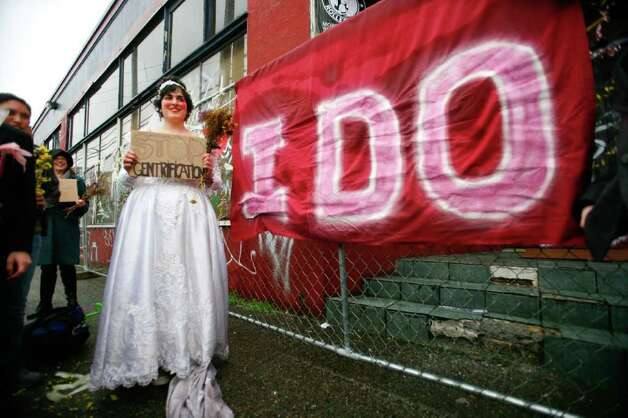 "Babylonia Aivaz stands in front of a large ""I Do"" banner during her marriage to the warehouse in the background at 10th Ave and Union St. on Sunday, Jan. 29, 2012. About 30 people attended Aivaz's wedding, which she says is a gay marriage because the building is a woman.  Aivaz, who was among the Occupy Seattle protesters who wanted to reclaim it as community space, is using the wedding to protest the demolition of the 107-year-old building. An apartment building will be built in its place. Photo: LINDSEY WASSON / SEATTLEPI.COM"