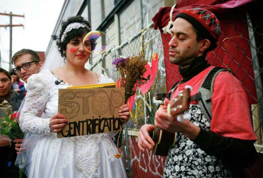 A bubble floats past Babylonia Aivaz as she listens to the band play at her wedding to the warehouse at 10th Ave and Union St. on Sunday, Jan. 29, 2012. About 30 people attended Aivaz's wedding, which she says is a gay marriage because the building is a woman. Aivaz, who was among the Occupy Seattle protesters who wanted to reclaim it as community space, is using the wedding to protest the demolition of the 107-year-old building. An apartment building will be built in its place. Photo: LINDSEY WASSON / SEATTLEPI.COM
